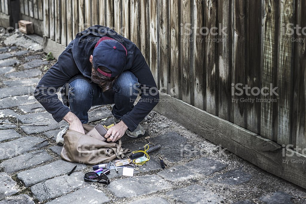 male thief looking into a stolen handbag stock photo