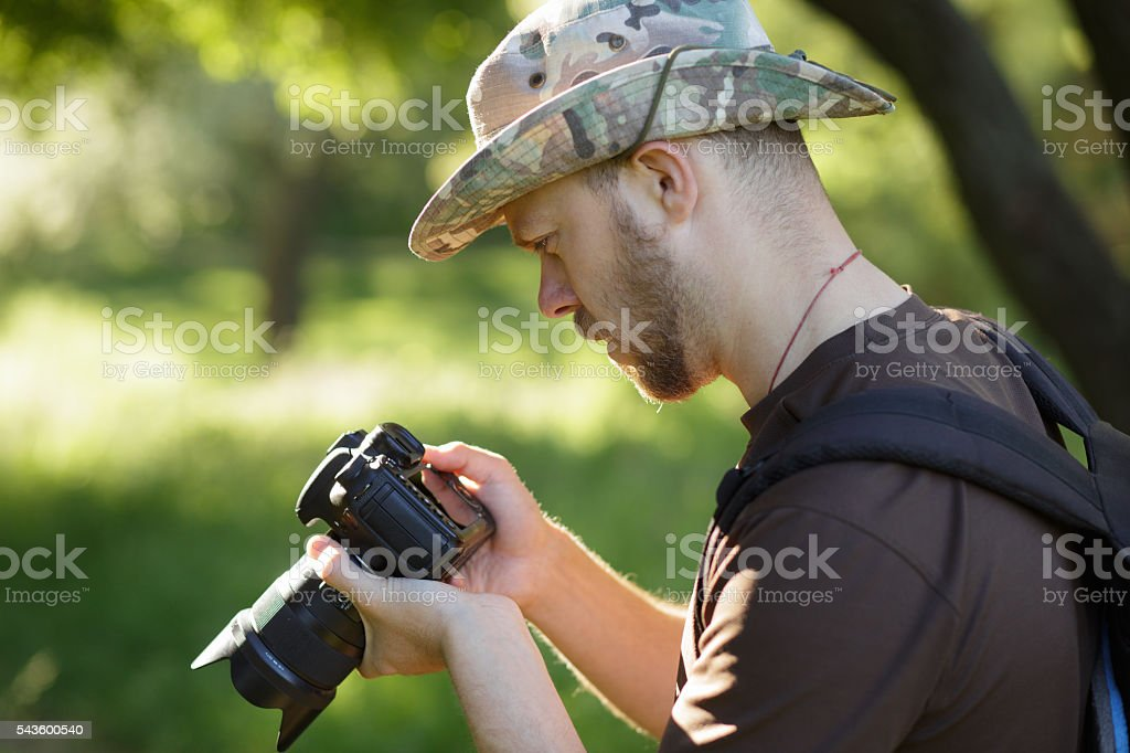 Male tourist looking captured photos at his DSLR camera outdoors stock photo