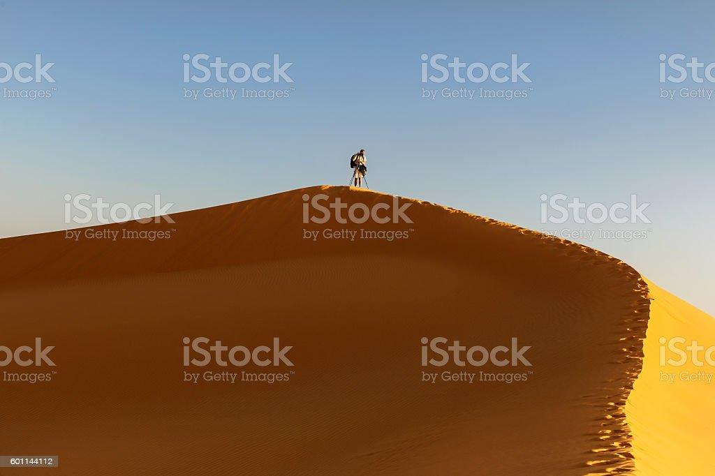 Male  tourist photographing, sand dunes, evening ,Erg Chebbi, Morocco stock photo