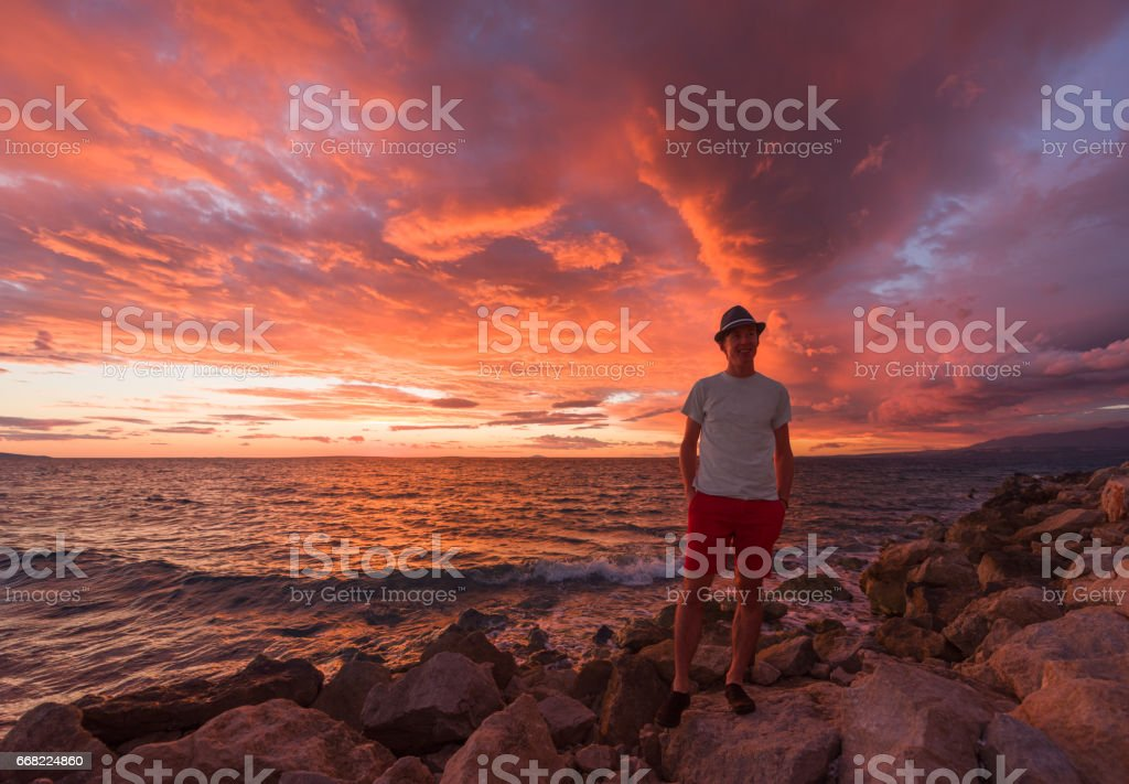 Male tourist relaxing on the beach during sunrise stock photo