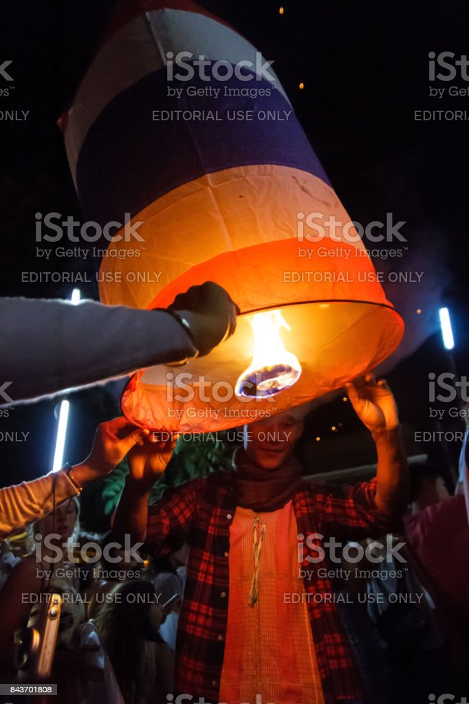 A male tourist releases a floating lantern in Chiang Mai, Thailand stock photo
