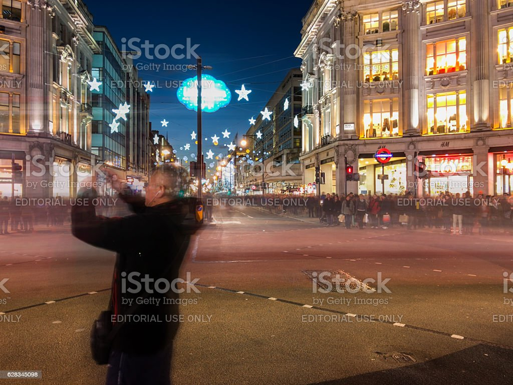 Male tourist taking photos at London Oxford Circus at night stock photo