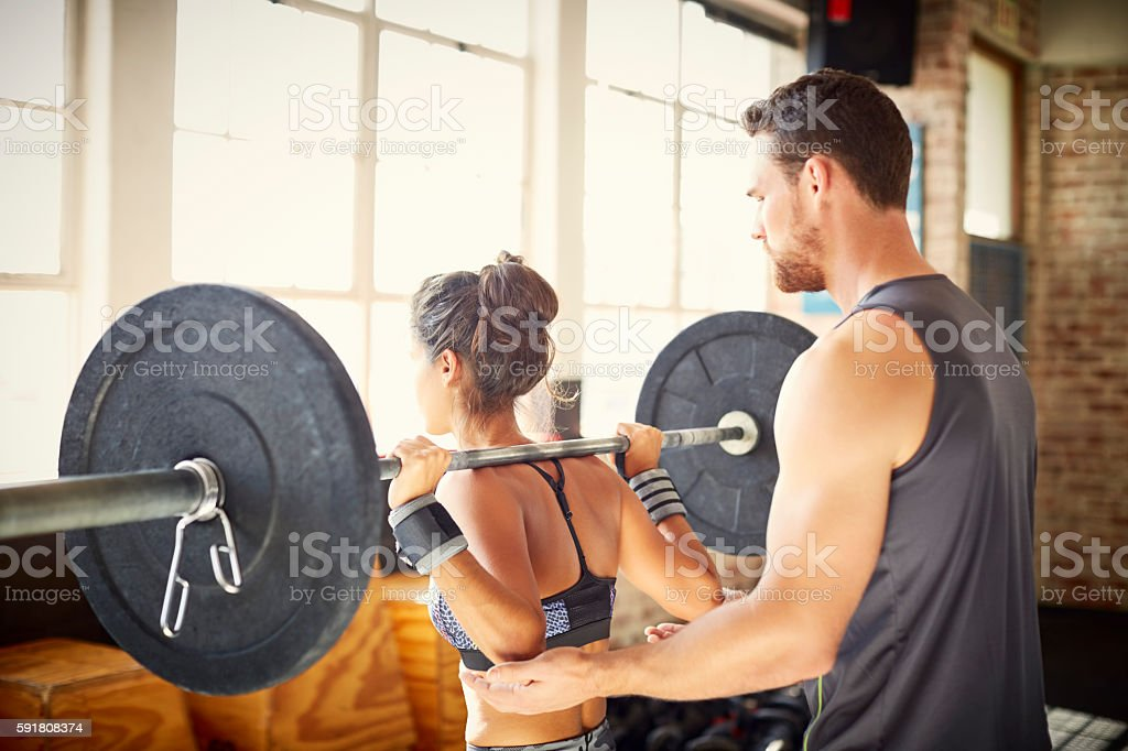 Male trainer assisting female customer in lifting barbell in gym stock photo