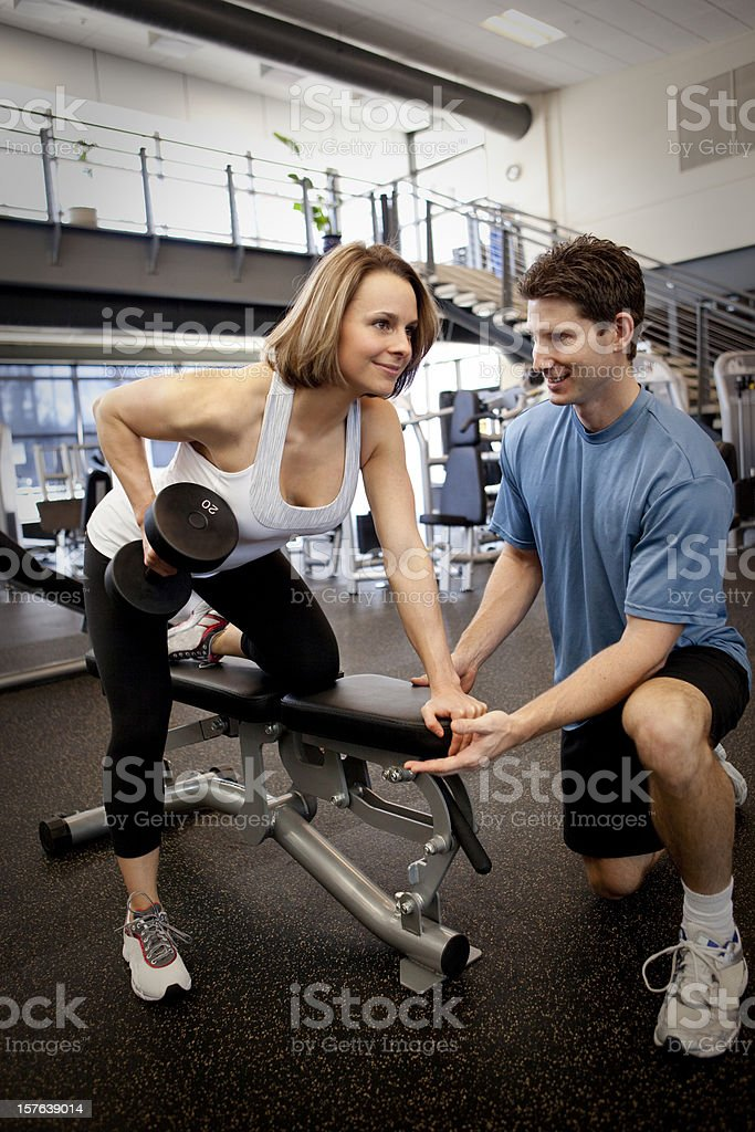 Male trainer working out a female client royalty-free stock photo