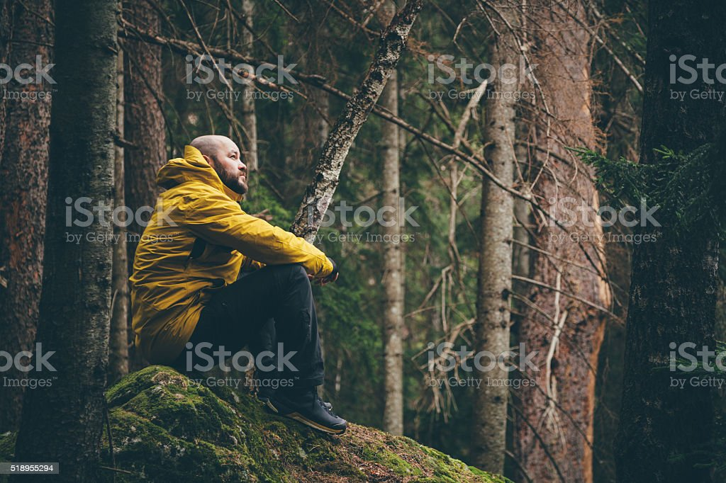 Male traveler in the forest, resting and looking around stock photo