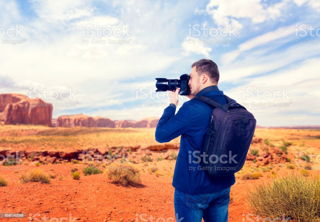 Male traveler photographing mountain valley stock photo