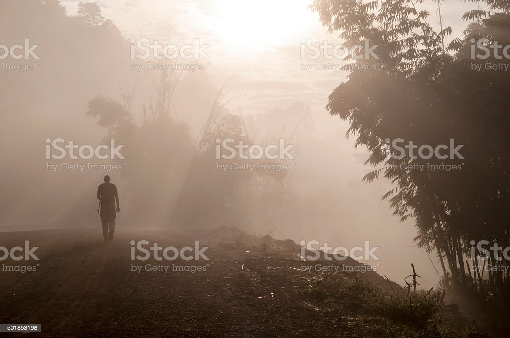 Male traveler trekking at sunrise in misty forest in Burma stock photo