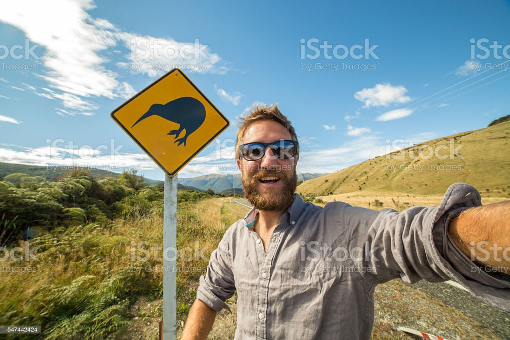 Male traveling takes selfie portrait with kiwi sign, New Zealand stock photo