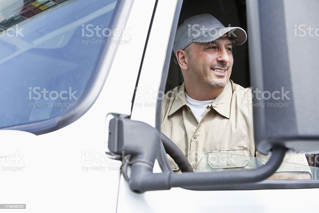 Male truck driver sitting in semi cab stock photo