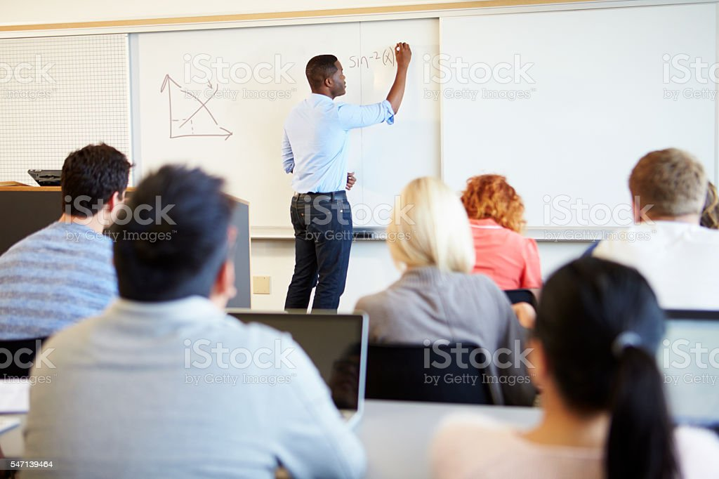Male Tutor Teaching University Students In Classroom stock photo