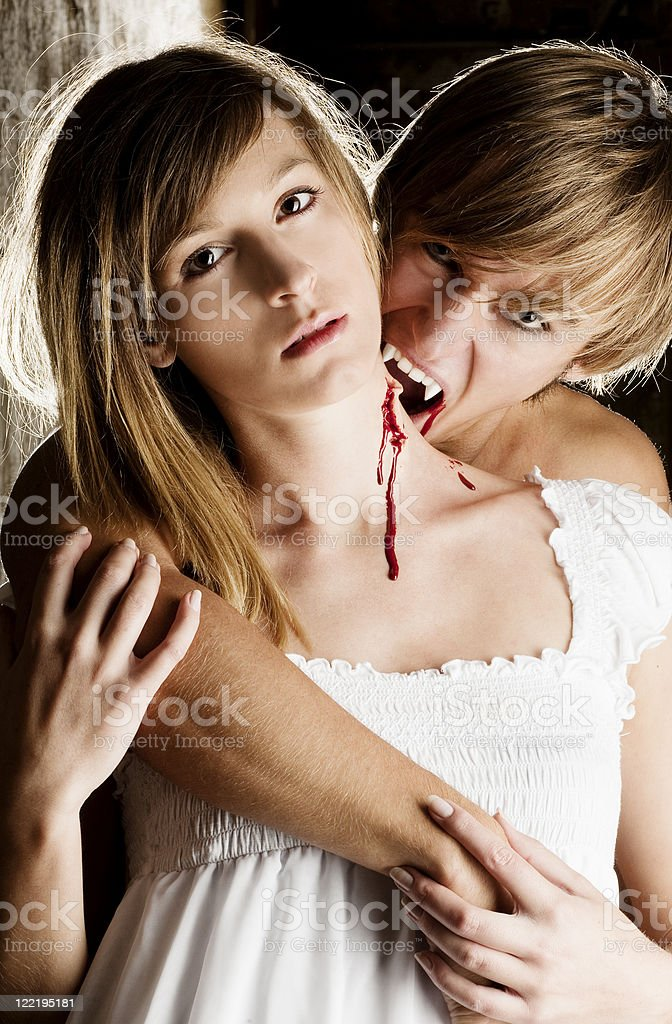 Male Vampire is biting a beautiful woman royalty-free stock photo