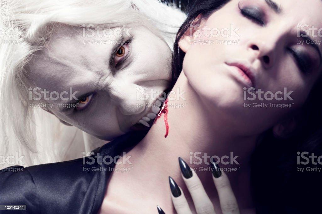 Male Vampire is biting a beautiful woman. stock photo
