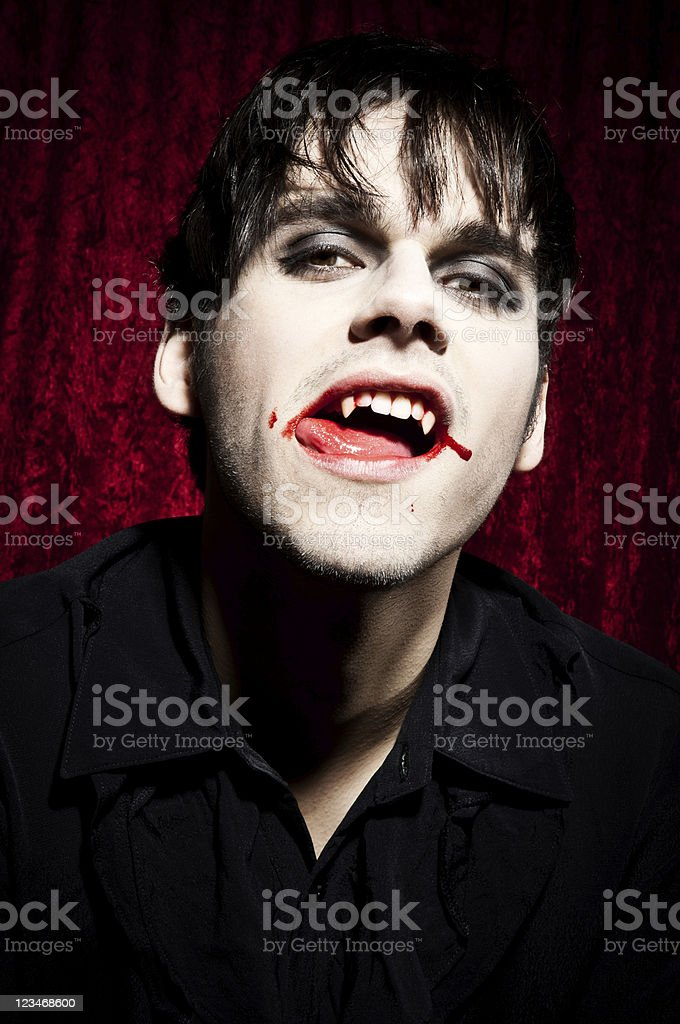 Male vampire is licking his bloody lips royalty-free stock photo
