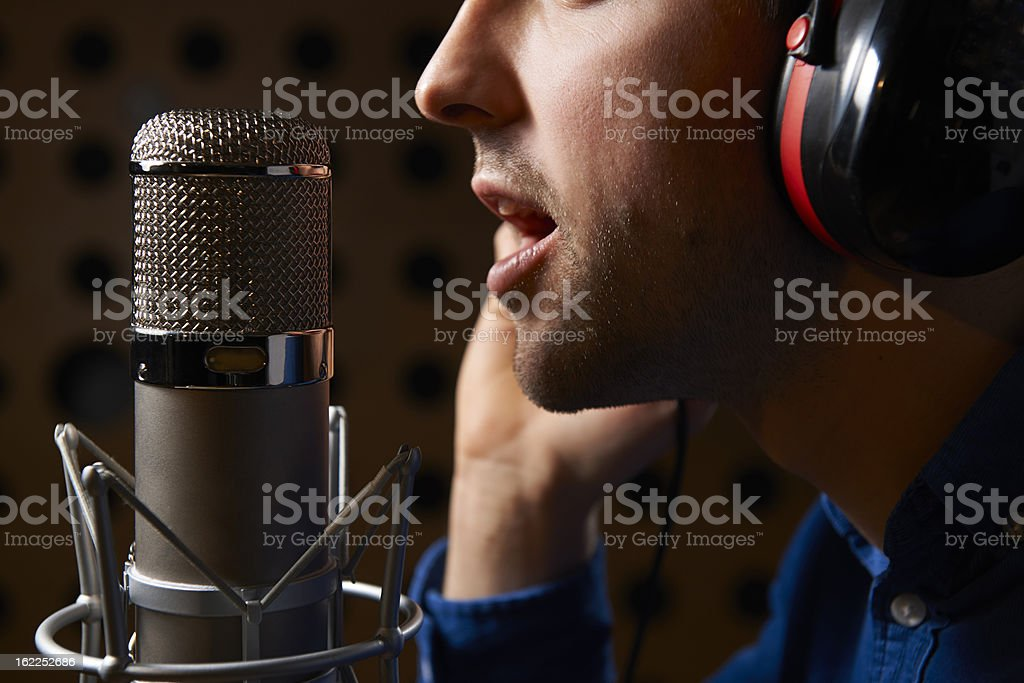 Male Vocalist Singing Into Microphone In Recording Studio royalty-free stock photo