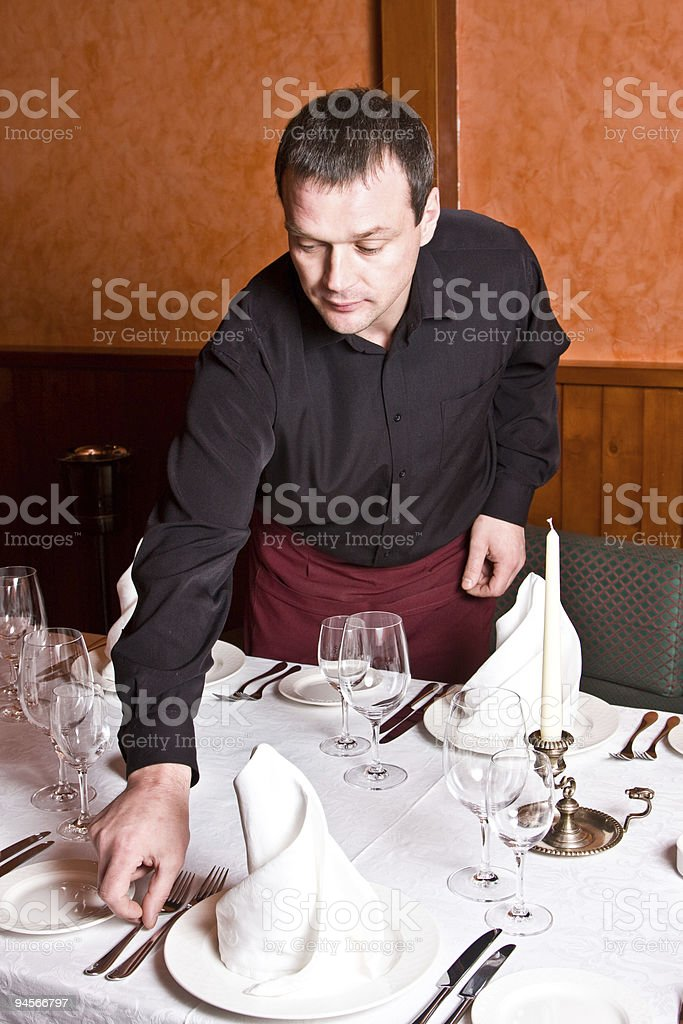 Male waiter arranges dishes on the table in a restaurant royalty-free stock photo