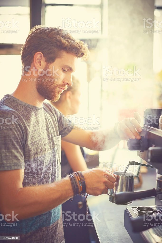 Male waiter holding milk jug in cafe stock photo