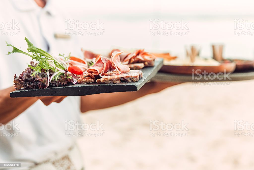 Male waiter serving beef carpaccio stock photo