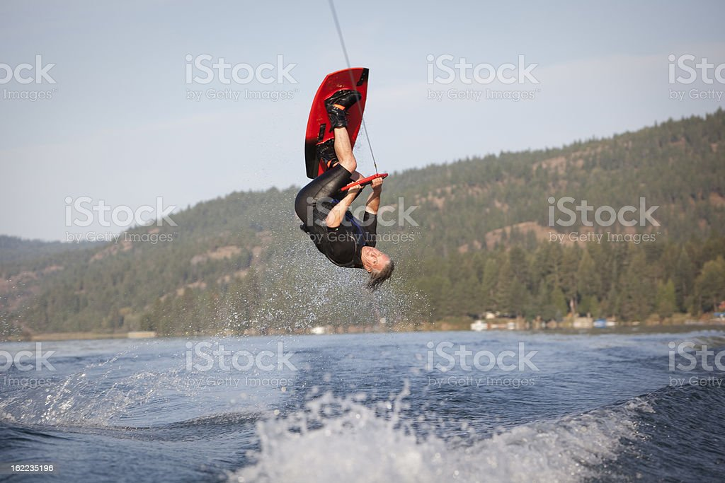 Male wakeboarder in the air doing a flip stock photo