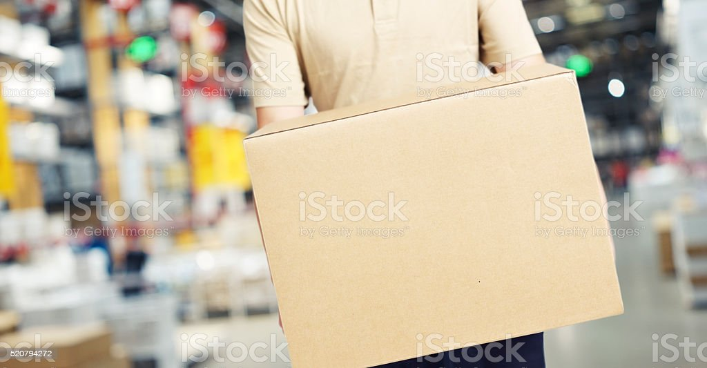 male warehouse worker carrying a carton box stock photo