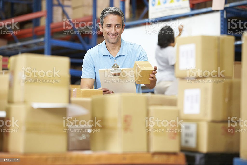 Male warehouse worker with a clipboard preparing shipment royalty-free stock photo