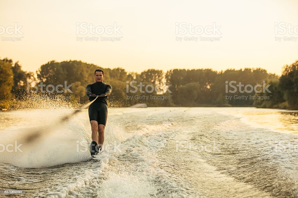 Male water skiing behind a boat on lake stock photo