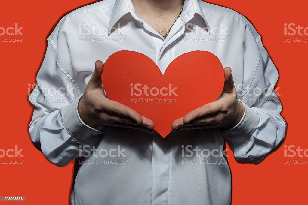 Male white shirt that holding a big red heart stock photo