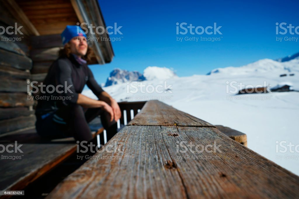 male winter sports athlete pausing in scenic alps landscape stock photo
