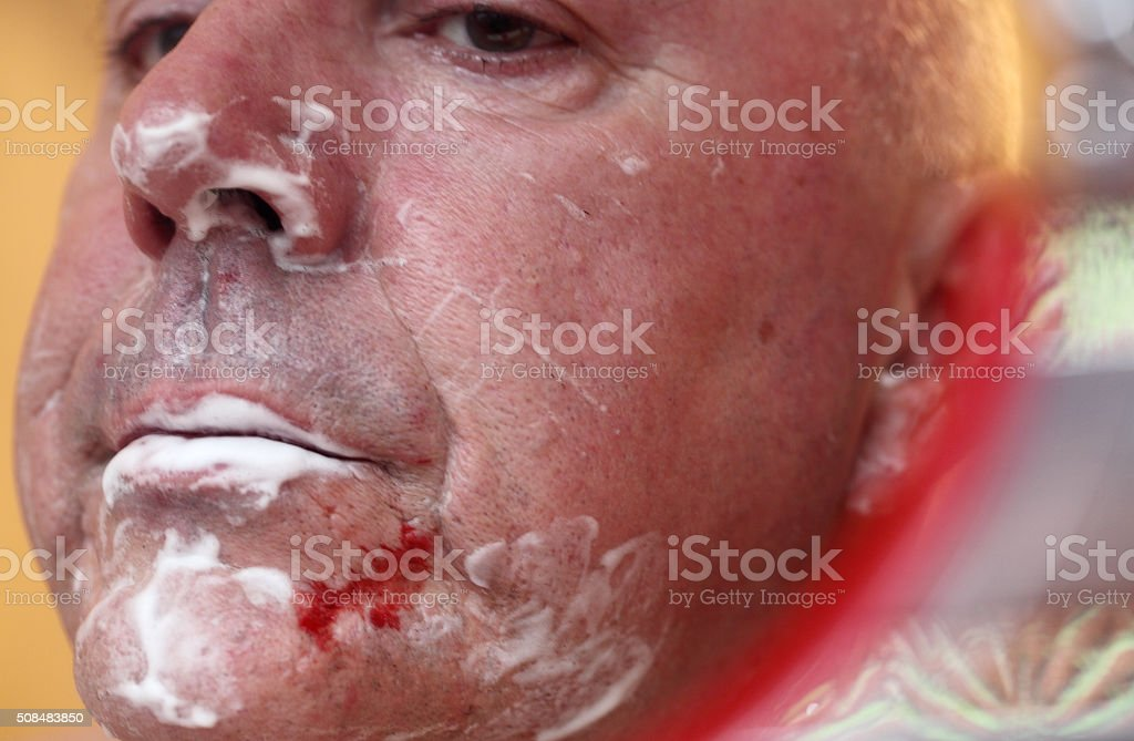 male with cut face during shaving stock photo