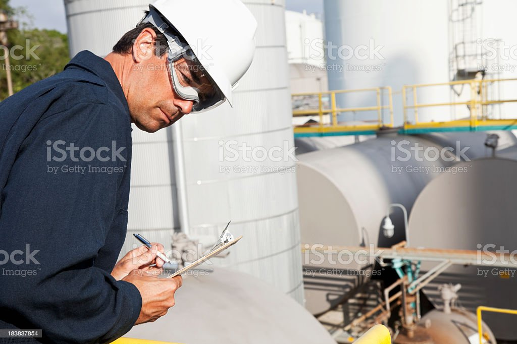Male worker at industrial plant writing on clipboard stock photo