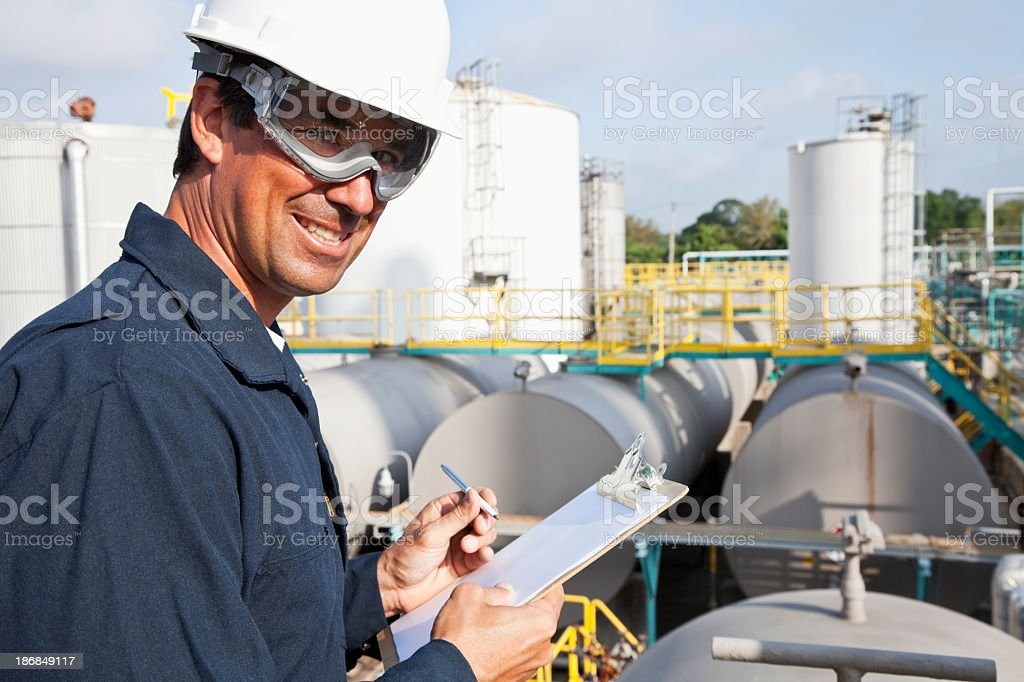 Male worker at industrial plant writing on clipboard royalty-free stock photo