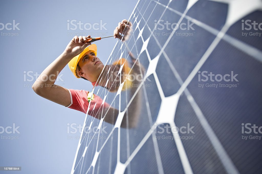 Male worker at work fixing solar panel stock photo