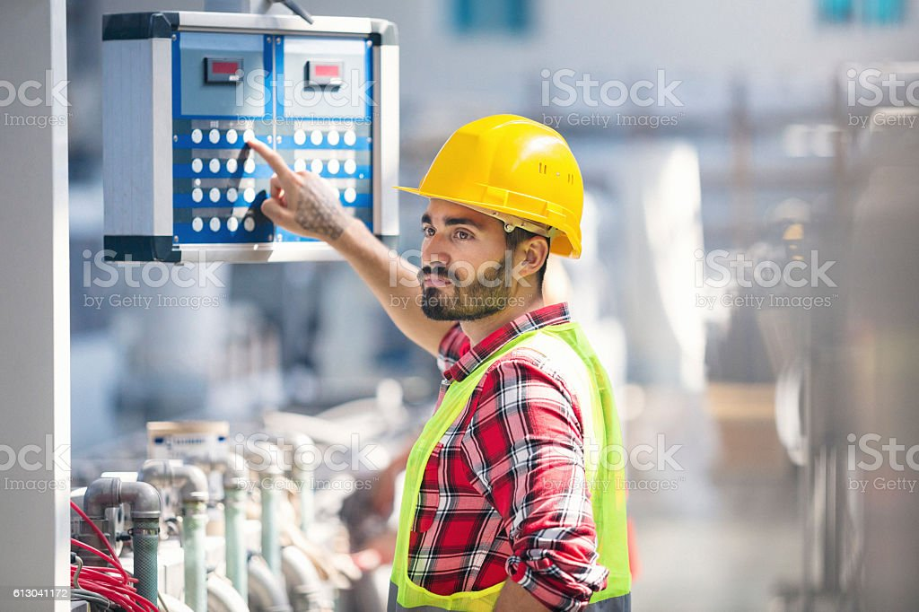 Male worker carefully operating a machine in factory stock photo