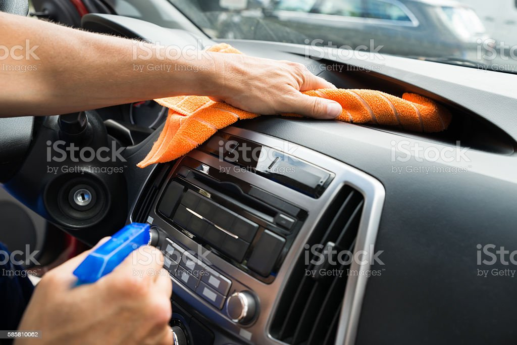 Male Worker Cleaning Car Dashboard stock photo