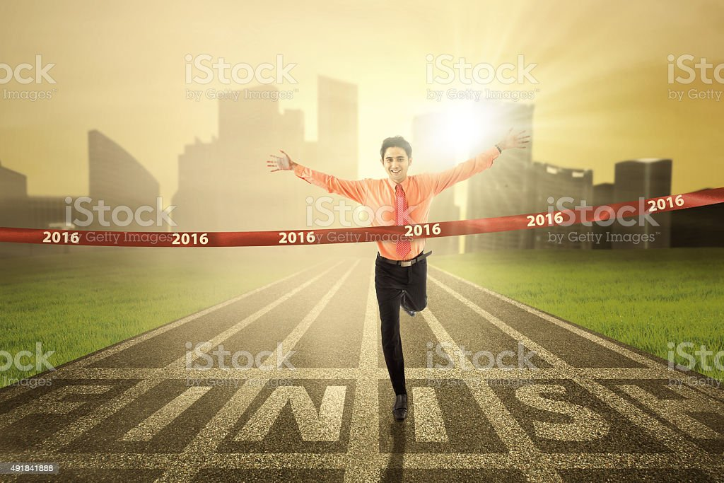 Male worker crossing the finish line stock photo