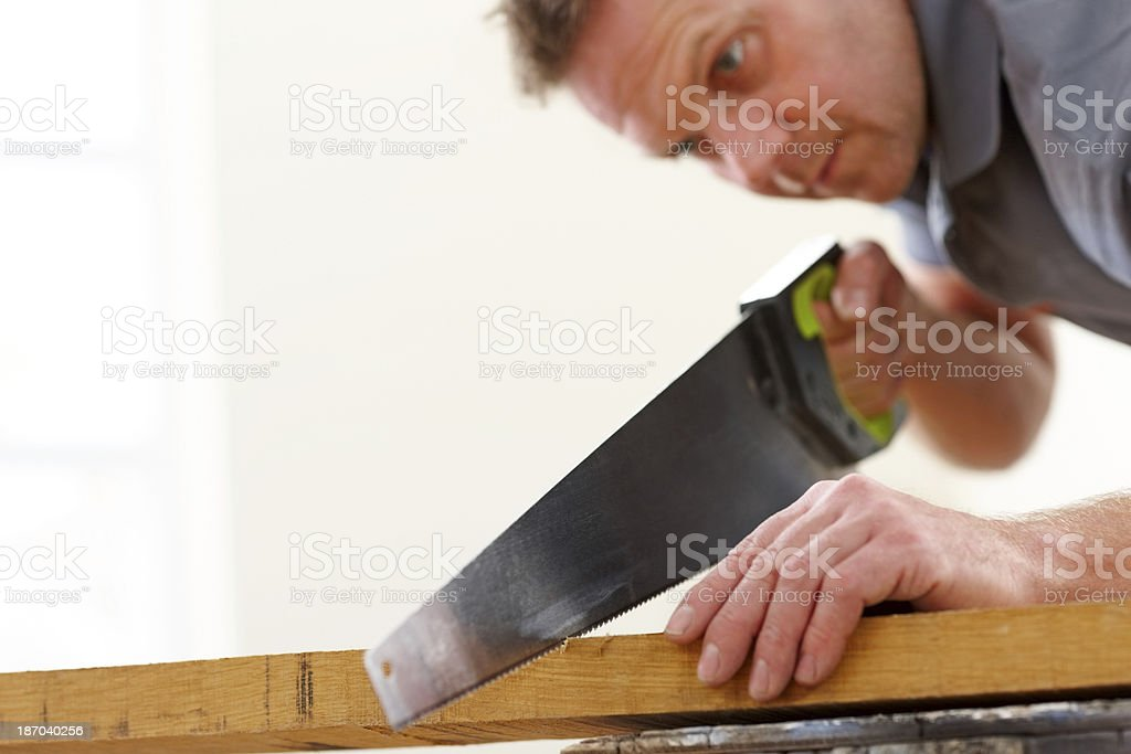 Male worker cutting wooden plank with a saw royalty-free stock photo