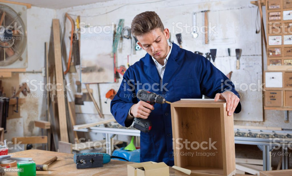 Male worker  finishing to drill drawer stock photo