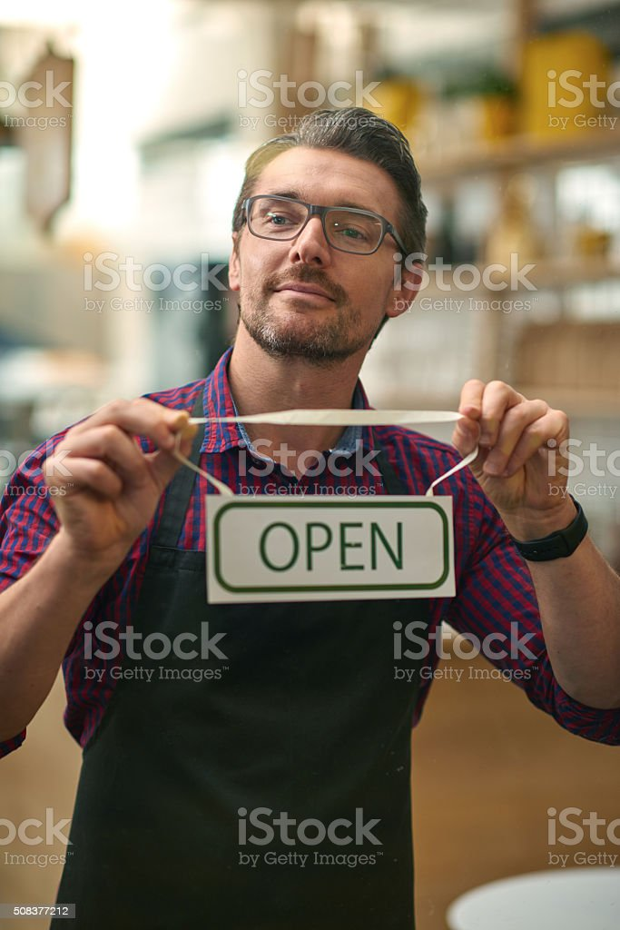 Male worker holding open sign through glass of cafe door stock photo