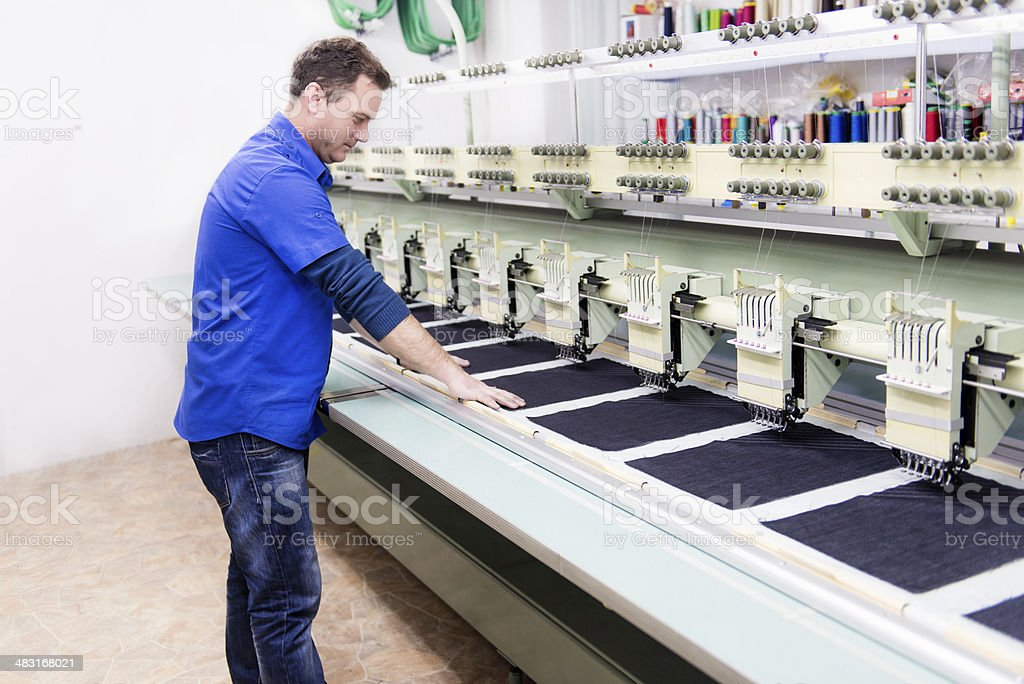 Male Worker how Set Automatic Embroidery Machine in Textile Factory stock photo