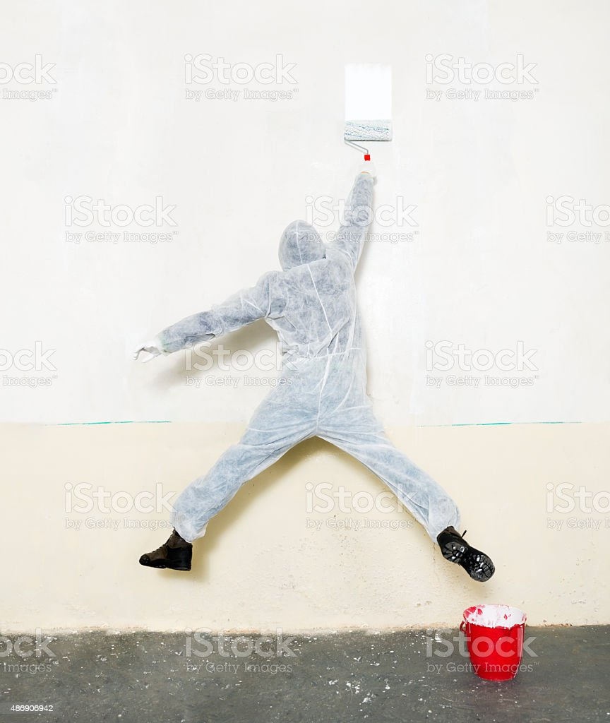 Male worker in a painting suit painting a white wall stock photo