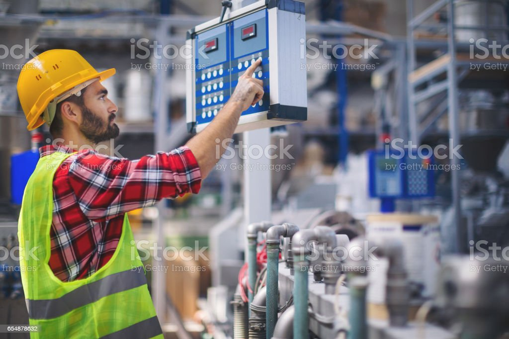 Male worker in factory operating a machine stock photo