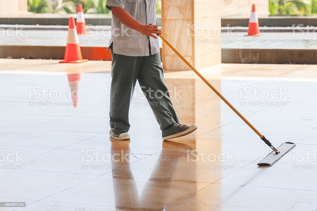 Male worker mopping the floor stock photo