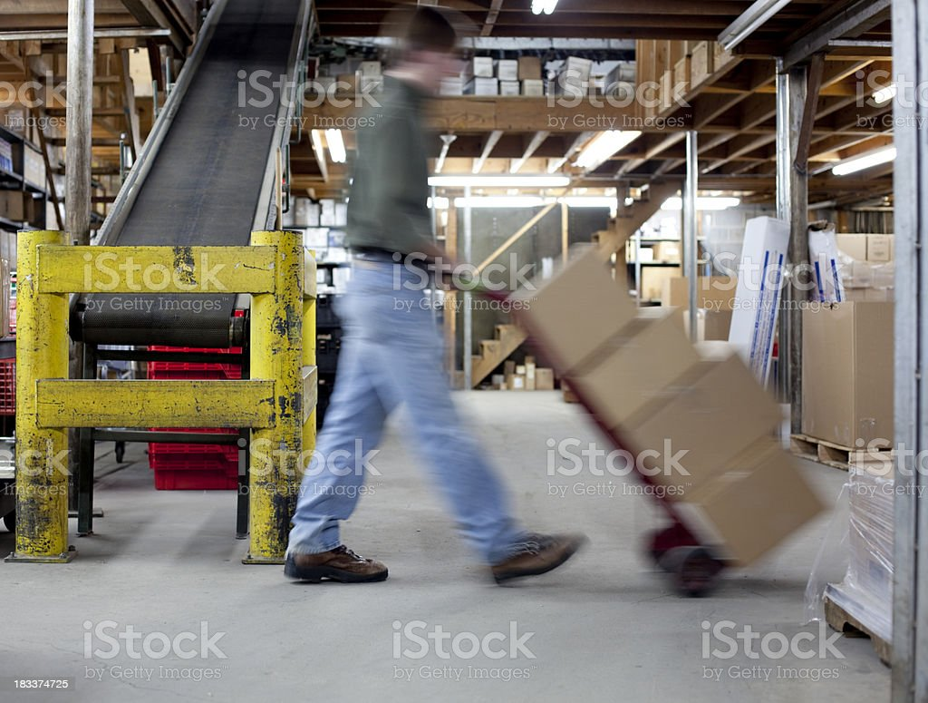 A male worker moving boxes throughout a warehouse royalty-free stock photo