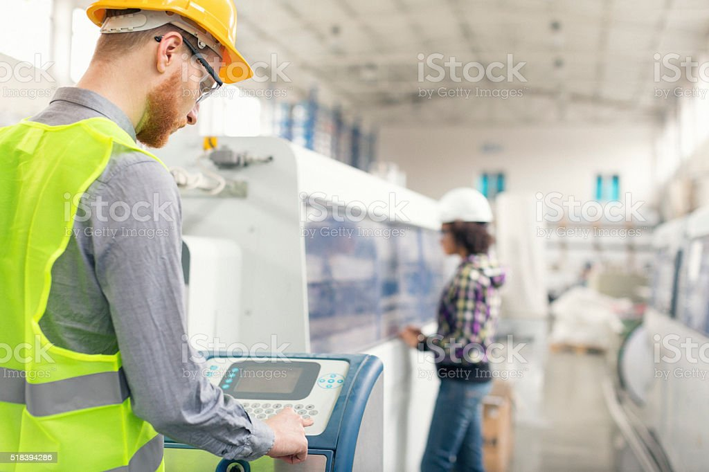 Male worker operating a machine in factory stock photo