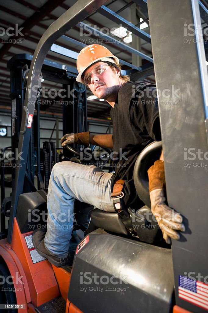 Male worker operating forklift in warehouse stock photo