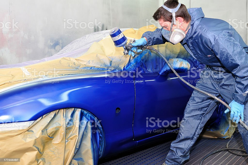 Male worker painting exterior of a blue car against wall stock photo
