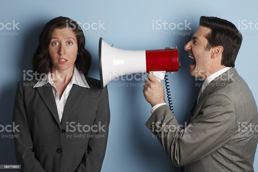 Male worker shouting at female worker using a megaphone stock photo