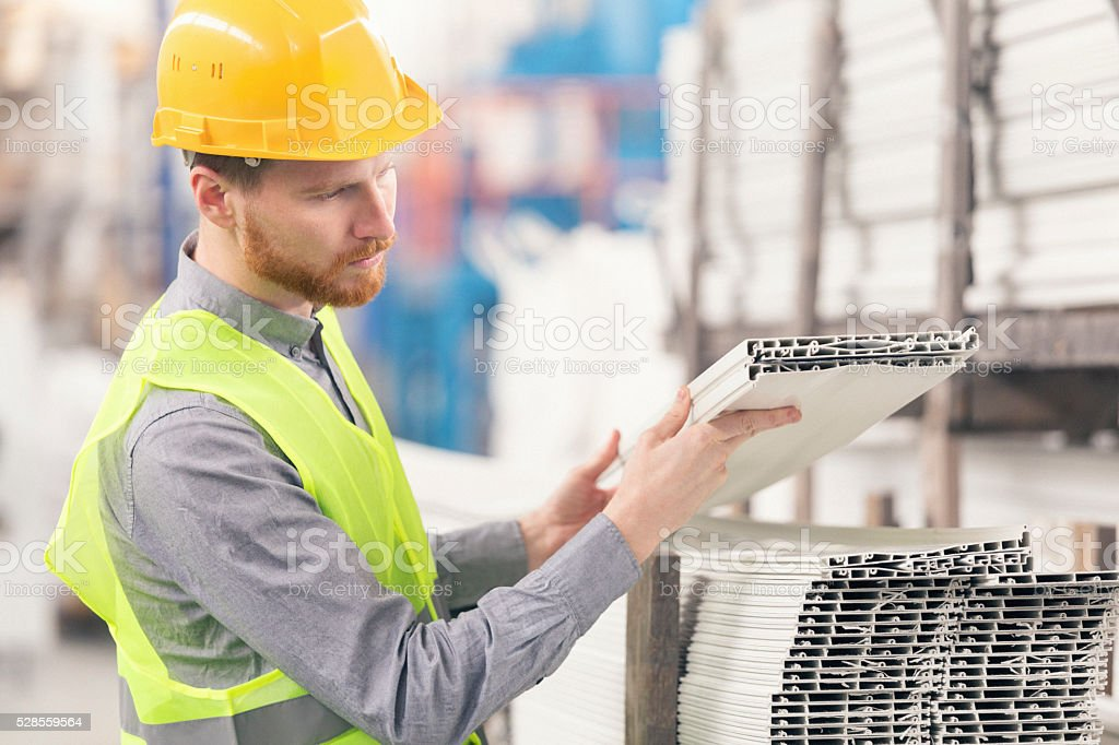 Male worker stacking plastic boards in the factory stock photo