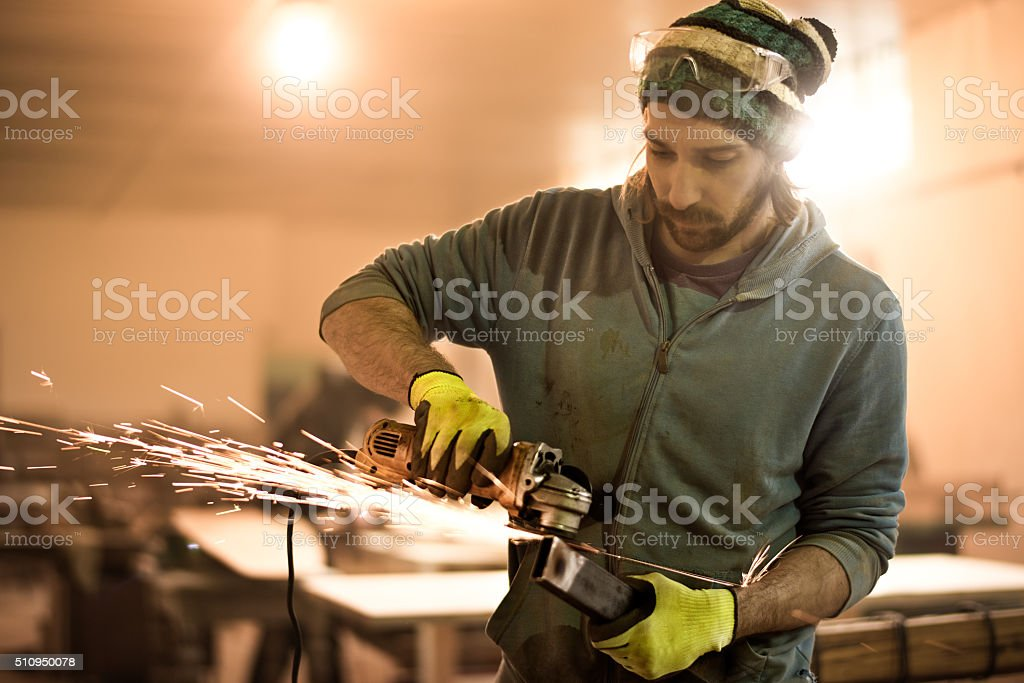 Male worker using grinder in workshop stock photo