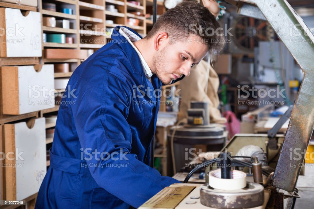 Male worker using machine for trimming at workshop stock photo