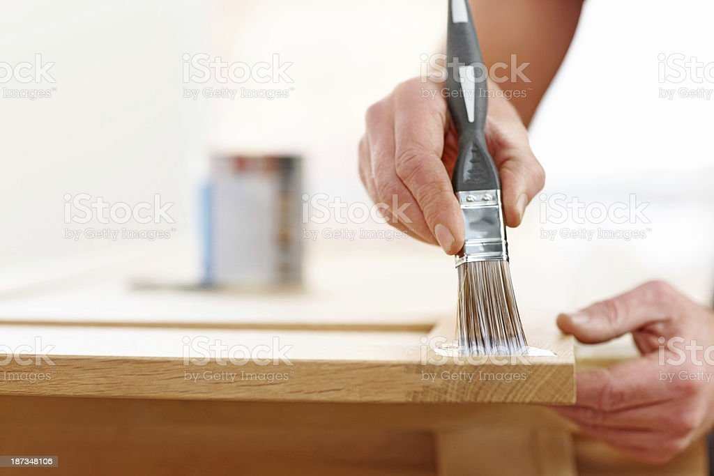 Male worker's hands applying wood stain stock photo